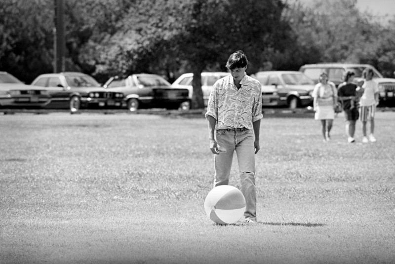 Steve Jobs Pretending to Be Human. Menlo Park, California, 1987. Steve was not the kind of guy who ever seemed to relax. He was usually focused like a laser on the task at hand. So it was surprising to see Steve kicking this beach ball around at a company picnic. He seemed to be having a good time, but it felt more like a performance designed to encourage the team to relax. He knew well from previous experience that his team needed breaks in order to sustain the forced march that would culminate in shipping the product.