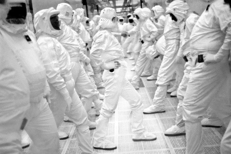 """Exercise Break at Intel Fab 11x. Rio Rancho, New Mexico, 1998. Workers inside Intel's largest chip fabrication plant exercise and stretch as part of their normal workday break time. They produce 5 chips a second, 24 hours a day. Many of the workers are from the nearby Pueblo tribe of Native Americans, who maintain their traditions when not working with new technology. After work, in good weather, many tend their corn and bean fields with their families before dinner. An industry powerhouse, they helped Microsoft Windows become the dominant operating system and today Intel chips run most of the PC's in the world. Founded by industry legends Gordon Moore and Robert Noyce, Andy Grove was their first employee. Moore posited """"Moore's Law"""" which predicted the number of transistors placed on chips would double approximately every two years. Noyce is co-creator of the microchip that gave Silicon Valley its name and which fueled its growth. Andy Grove become CEO and led Intel through a long period of tremendous growth. He became a mentor to Steve Jobs as Jobs began his quest for redemption after Apple. Although Jobs hated Microsoft Windows and was unhappy about Intel's support of Microsoft, he acknowledged the Pentium chip as a true innovation and said it was"""